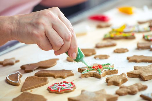 Partial view of woman icing Christmas cookies