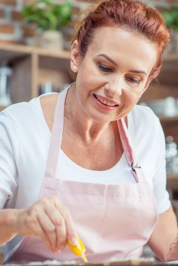 Smiling woman icing Christmas cookies at home