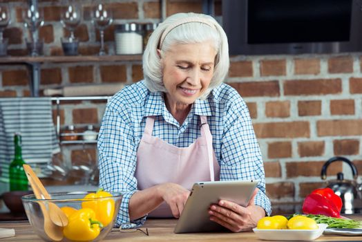 Smiling senior woman in apron using digital tablet in kitchen