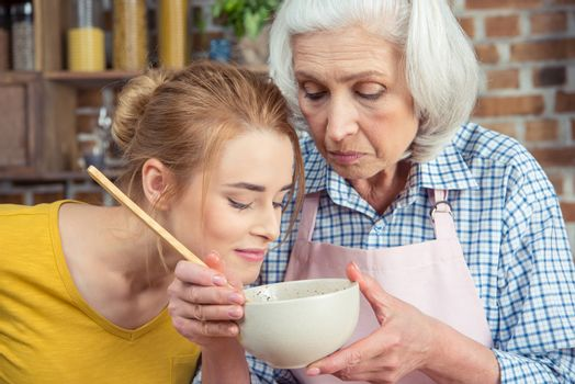 Granddaughter and grandmother cooking together and looking into bowl