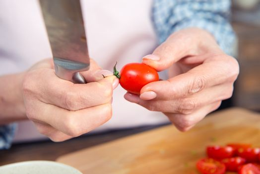 Close-up partial view of woman holding knife and tomato