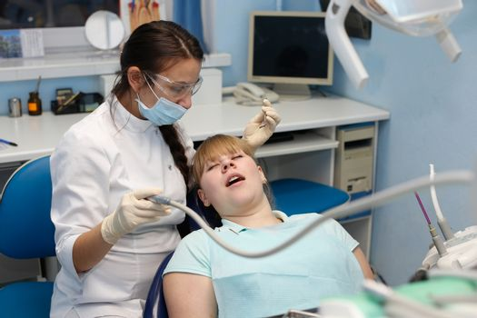 Dentist in a private office holds reception of the patient with pain. The Dentist Selects The Tool And Starts Examination Of The Teeth.