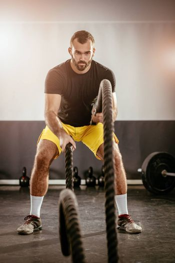 Young man exercising with ropes at the gym.