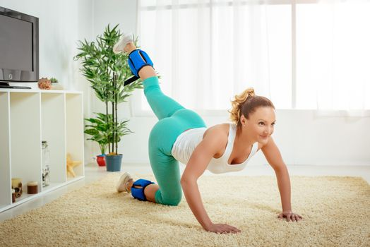 Beautiful young woman doing exercise with dumbbells at home.