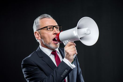 Mature businessman with loudspeaker