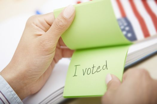 Human hands holding adhesive note with I voted text