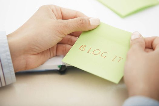 Hands holding sticky note with Blog it text