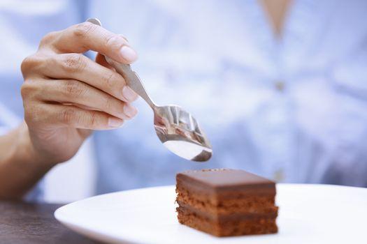Hand of woman eating chocolate cake