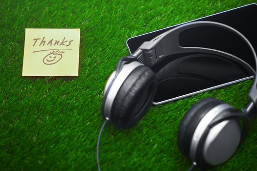Thanks text on sticky note on a grass with headphones and digital tablet