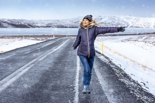 Young people traveling in winter, active girl enjoying road trip, jumping on the road in snowy wintertime day, tourist in Iceland