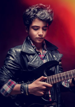 Teen guy playing on guitar