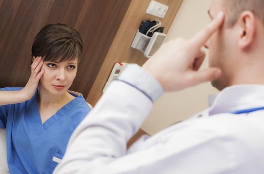 A female patient with headache in hospital worried is looking at doctor pointing his head.