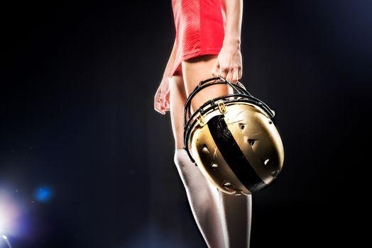 Female football player holding helmet