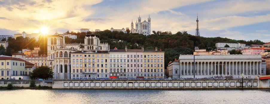 Colorful, cloudy sunset over Vieux Lyon and Fourviere Basilica seen from the riverbank of the Saone, Lyon.