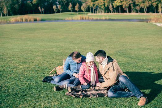 Beautiful family sitting on green meadow