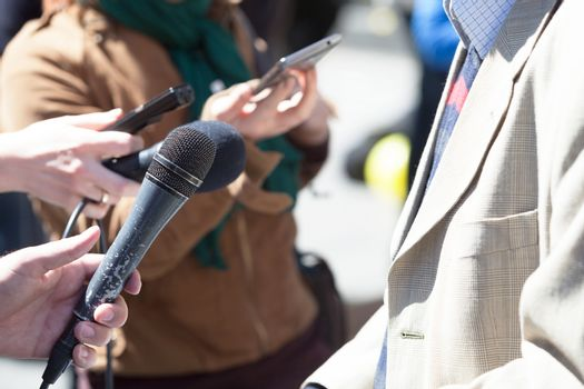Reporter holding a microphone conducting an media interview