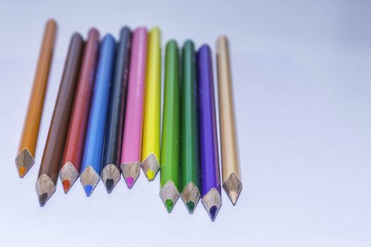 Colored crayons on the white background, school
