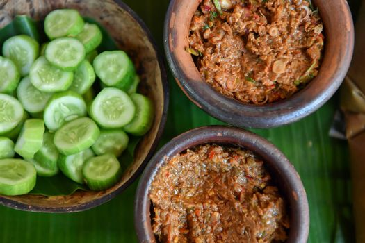 Fermented fish spicy dip in bowl baked clay with fresh cucumber, Thai food. traditional fish preservation,
