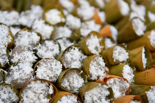 Bananas cake in leaf cone and sprinkle with coconut, Thai traditional dessert.