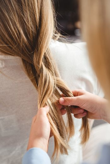 Daughter plaiting braid of mother