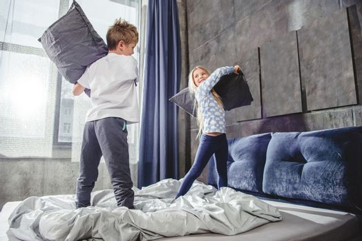 Siblings fighting with pillows