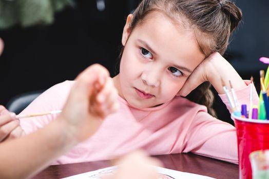 Bored schoolchild sitting at table