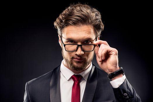 Businessman adjusting eyeglasses