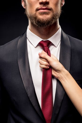 Woman holding businessman by tie