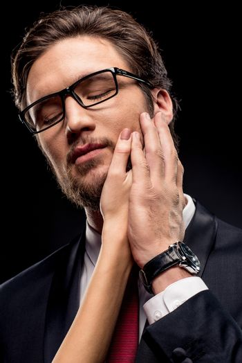 Businessman with female hand on face