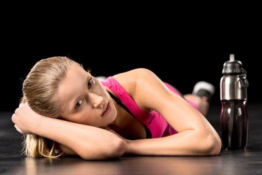 Sportswoman resting on floor