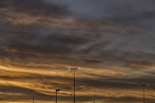Sunrise with Street Lights on a cloudy sky.
