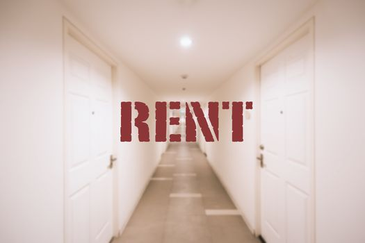 Red RENT word in center of blurry background of corridor inside white building in orange tone lamp.