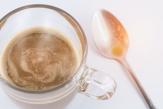 Close focus on hot coffee in clear glass cup on white table. Blurry teaspoon and orange warm sunlight as background.