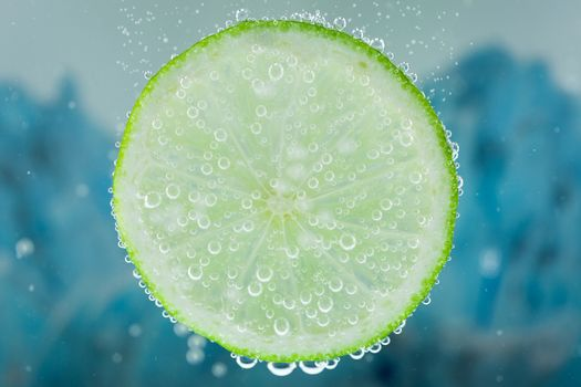 Close-up of lime green slice on blue background diving inside carbonated water with bubbles