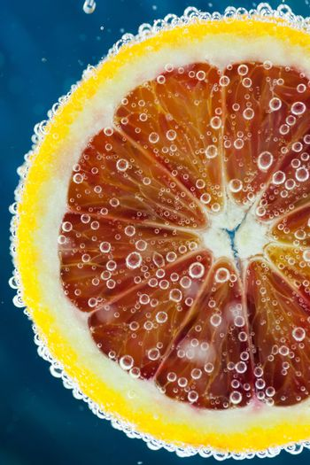Close-up of slice of citrus blood orange dropped into carbonated water with bubbles on blue background