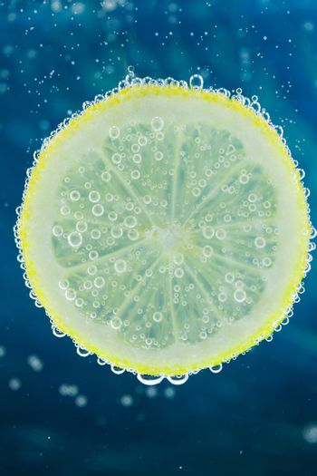 Vertical close-up of slice of lemon falling into carbonated water with bubbles, on blue background. Refresher drink concept