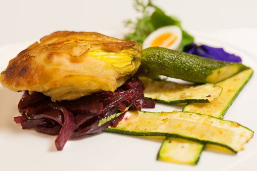 Delicious gourmet plate featuring biscuit sandwich with beets, zucchini strips and pansy garnish over white background
