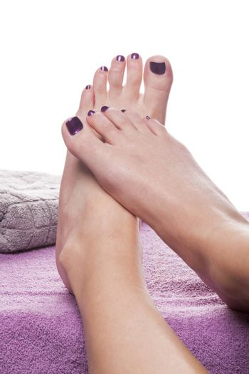 Bare feet with pedicure propped by towel on soft purple treatment table against white background