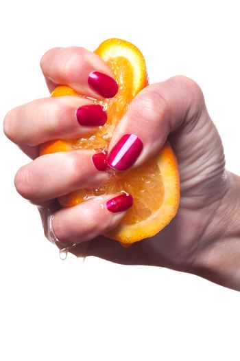 Hand with manicured nails painted a deep glossy red touch an orange on white background