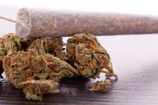Close up of dried marijuana leaves and tied end of marijuana joint with translucent rolling paper on white background