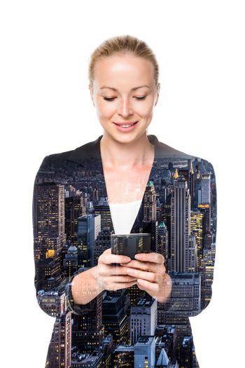 Beautiful young caucasian businesswoman in business attire using smart phone application. Double exposure with panorama of new York City overlay.