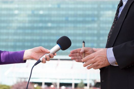 Reporter interviewing businessman, corporate building in background
