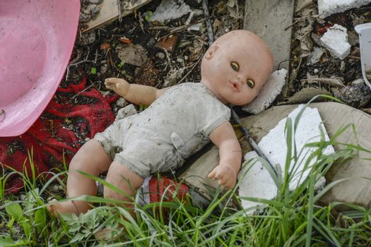doll lies abandoned on a garbage dump