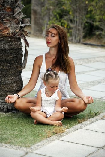 Mum with a small daughter do yoga