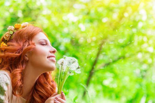 Happy woman with dandelion flowers