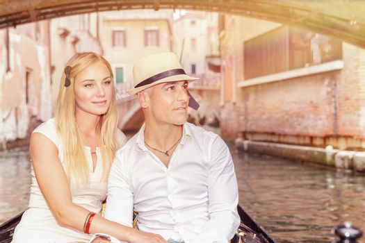 Portrait of a nice couple sitting in the gondola and enjoying wonderful trip along canal on narrow Venice street, romantic travel to Italy, Europe