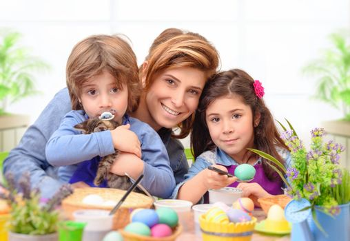 Portrait of happy family preparing to Easter, mother with two cute kids dyeing eggs, traditional Easter symbol, having fun together at home