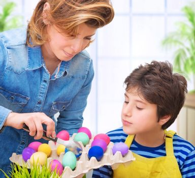 Mother teach her cute son to paint eggs for Easter holiday, having fun at home and with pleasure coloring eggs, happy family tradition