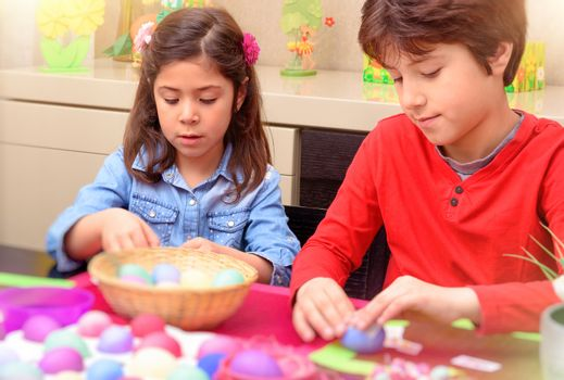 Brother and sister coloring Easter eggs