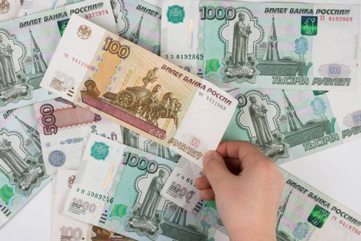 Children's hand takes the denomination from the pile of randomly scattered Russian banknotes of different denomination